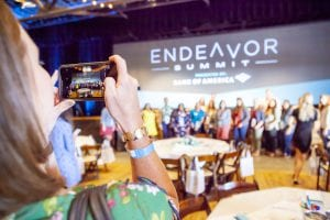 Female taking a group photo with a her phone of people in front of the endeavor summit logo