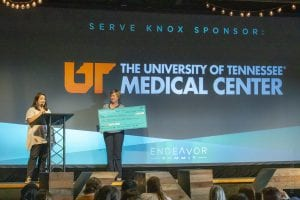 "Two females on stage at a podium holding a check in front a black background that reads ""The university of tennessee medical center"""
