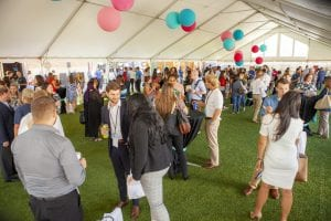 Crown networking underneath white tent with colorful balloons as decorations