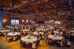 Crowd sitting at circular tables inside endeavor summit venue
