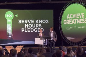 """Speakers on stage in front of a screen that reads """"serve knox hours pledged"""""""