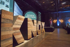 Knox wood decorations line the stage of a presenter