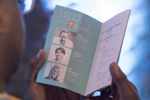 A person reading the book that describes endeavor summit's keynote speakers