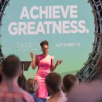 "Business woman presenting to a crowd in front of a sign that reads ""achieve greatness"""