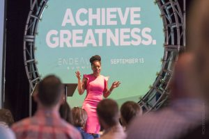 """Business woman presenting to a crowd in front of a sign that reads """"achieve greatness"""""""