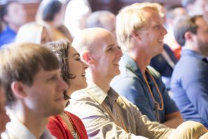 People at endeavor summit smiling as they listen to a presenter
