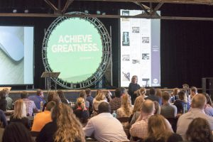 """Picture of crowd from the side as they view an image on stage that says """"achieve greatness"""""""