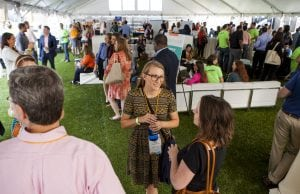 People networking underneath a tent outside