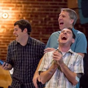 Three men laughing as they present