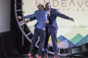 keynote speakers chest bumping at endeavor summit